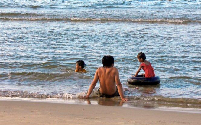 Phút giây yên bình cùng con ở bãi tắm Khe Hai – Ảnh: VÕ QUÝ CẦU