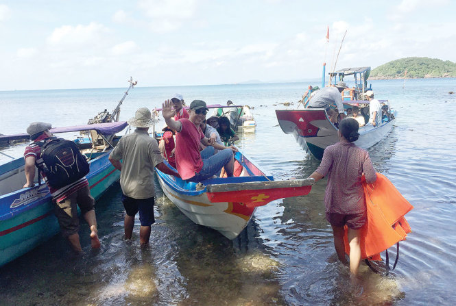 Cô Tám xắn quần lội xuống biển đẩy ghe, canô tiễn khách - Ảnh: Ng.Triều